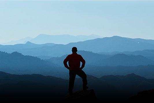 A man standing at the top of a mountain admiring the view
